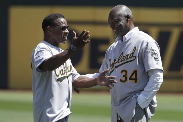 Former Oakland Athletics player Rickey Henderson, left, gestures next to former teammate Dave Stewart before a baseball game between the Athletics and the San Francisco Giants in Oakland, Calif., Sunday, Aug. 25, 2019. (AP Photo/Jeff Chiu)
