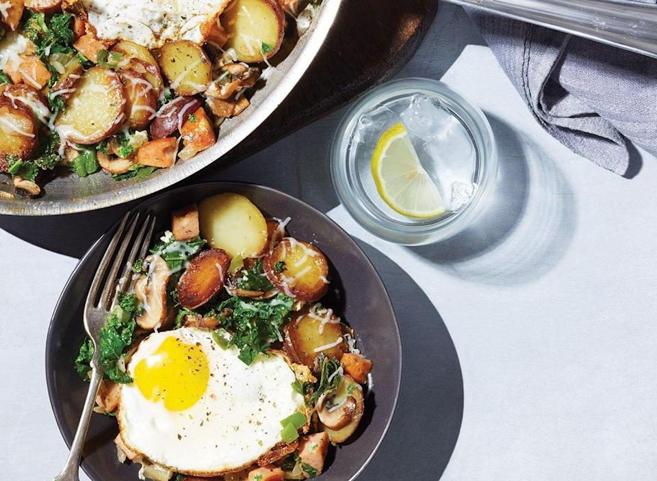 plate of italian hash with fried egg next to skillet and water glass