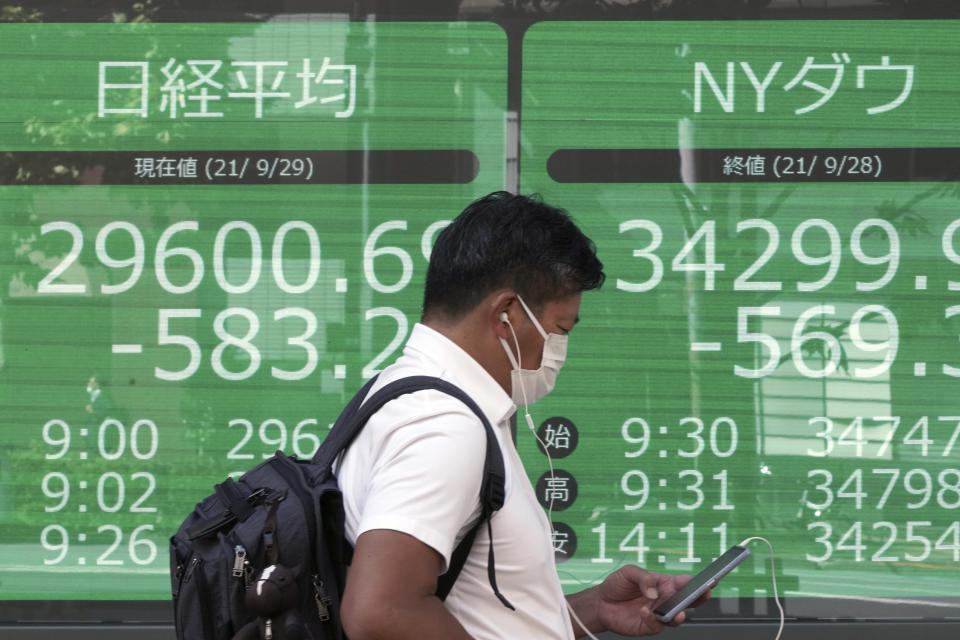 A man wearing a protective mask walks in front of an electronic stock board showing Japan's Nikkei 225 and New York Dow indexes at a securities firm Wednesday, Sept. 29, 2021, in Tokyo. Asian shares fell sharply on Wednesday after a broad slide on Wall Street as investors reacted to a surge in U.S. government bond yields. (AP Photo/Eugene Hoshiko)
