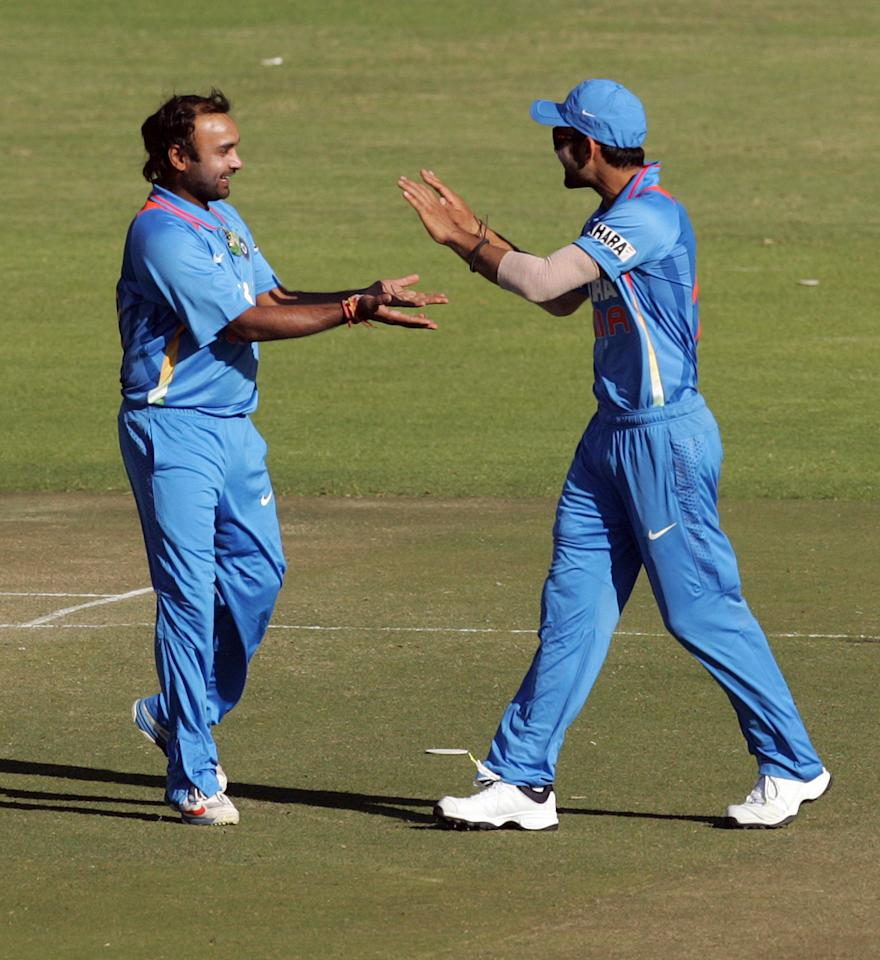 Indian bowler Amit Mishra (L) celebrates a wicket with team captain Virat Kohli (R)  during the second one-day international ODI series between hosts Zimbabwe and India at Harare Sports Club on July 26, 2013. AFP PHOTO / Jekesai Njikizana.        (Photo credit should read JEKESAI NJIKIZANA/AFP/Getty Images)