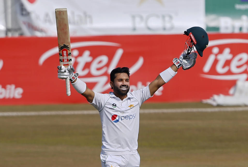 Pakistan's Mohammad Rizwan raises bat and helmet to celebrate after completing his century during the fourth day of the second cricket test match between Pakistan and South Africa at the Pindi Stadium in Rawalpindi, Pakistan, Sunday, Feb. 7, 2021. (AP Photo/Anjum Naveed)