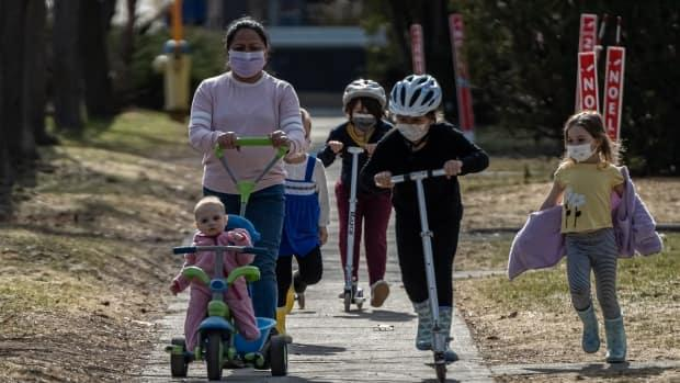 A group that's mostly in masks heads down an Ottawa pathway on March 30, 2021. (Brian Morris/CBC - image credit)