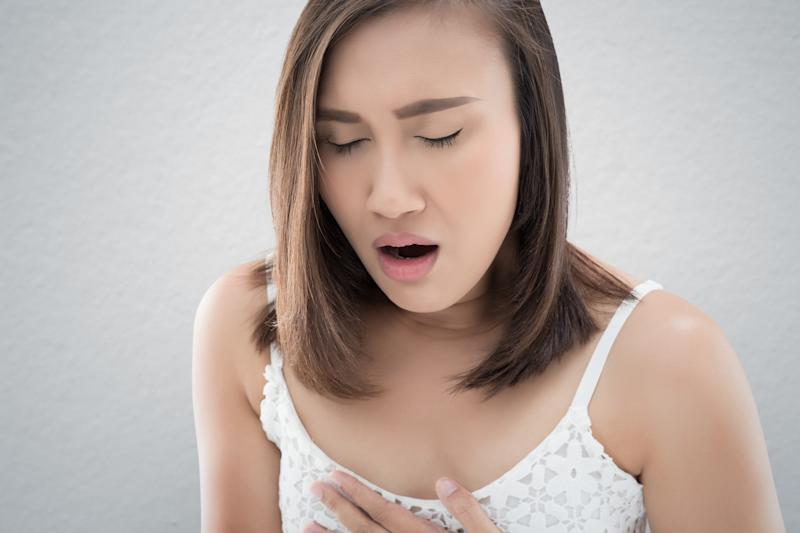 Asian women are vomiting because of morning sickness. Nausea or Vomiting. Have a headache against gray background.