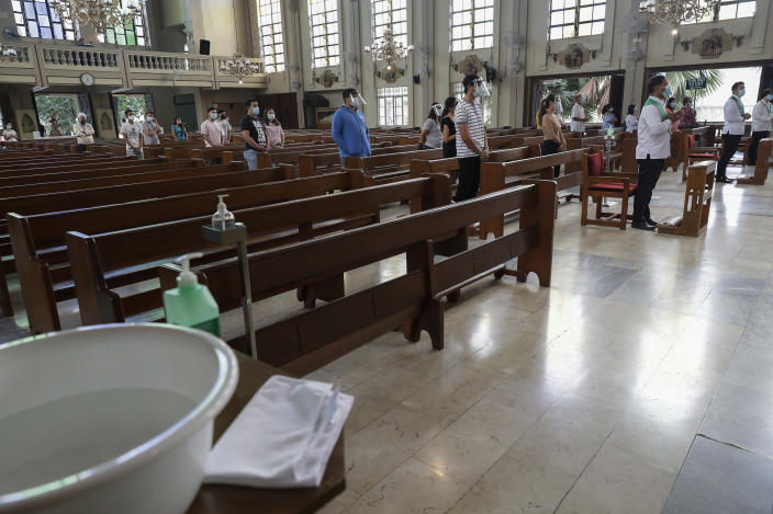 Disinfectants are placed around a church as parishioners keep their distance to curb the spread of COVID19 during a Mass at the Our Lady of Consolation Parish on Sunday, Aug. 2, 2020, in Quezon city, Philippines. Coronavirus infections in the Philippines continues to surge Sunday as medical groups declared the country was waging a losing battle against the contagion and asked the president to reimpose a lockdown in the capital. (AP Photo/Aaron Favila)