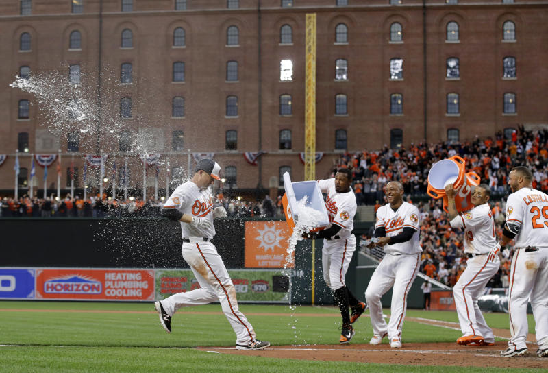 Baltimore Orioles' Mark Trumbo, left, is hit with ice water by teammates Adam Jones, Jonathan Schoop, Manny Machado and Welington Castillo as he runs toward home plate after hitting a solo home run in the 11th inning of an opening day baseball game against the Toronto Blue Jays in Baltimore, Monday, April 3, 2017. Baltimore won 3-2 in 11 innings. (AP Photo/Patrick Semansky)