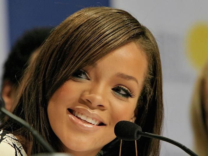 Rihanna speaks into a microphone at a news conference in 2006