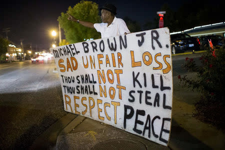 Ferguson resident Curtis Sadler holds a placard as he gathers with other protesters across the street from the police department in Ferguson, Missouri September 26, 2014. REUTERS/Whitney Curtis