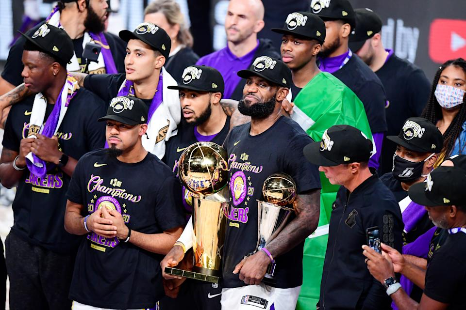LeBron James smiles while holding the MVP and NBA Finals trophies.