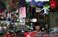 In this April 10, 2019, photo, a shopkeeper waits for business in Nuku'alofa, Tonga. China is pouring billions of dollars in aid and low-interest loans into the South Pacific, and even in the far-flung kingdom of Tonga there are signs that a battle for power and influence among much larger nations is heating up and could exact a toll. (AP Photo/Mark Baker)