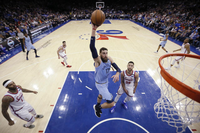 Memphis Grizzlies' Jonas Valanciunas (17) goes up for a dunk past Philadelphia 76ers' Ben Simmons (25) during the first half of an NBA basketball game Friday, Feb. 7, 2020, in Philadelphia. (AP Photo/Matt Slocum)