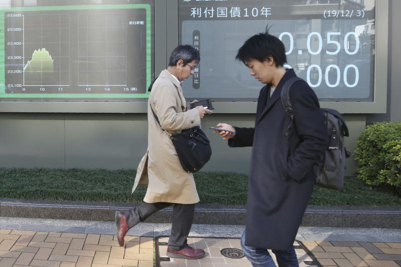 People walk by an electronic stock board of a securities firm in Tokyo, Tuesday, Dec. 3, 2019. Asian shares slipped Tuesday, following a drop on Wall Street amid pessimism over U.S.-China trade tensions. (AP Photo/Koji Sasahara)