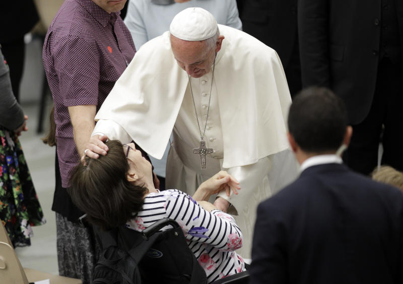 Pope Francis caresses a sick woman during an audience with Huntington's disease sufferers and their families, in the Paul VI Hall, at the Vatican, Thursday, May 18, 2017. Francis is trying to end the stigma of people afflicted with Huntington's Disease, an incurable genetic brain disorder that causes such serious involuntary movements and psychiatric problems that sufferers are often shunned and isolated. (AP Photo/Andrew Medichini)