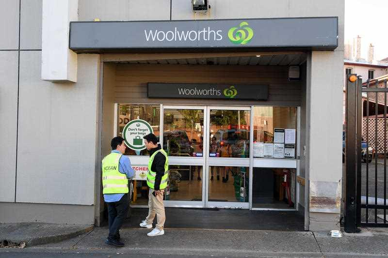 Cleaning contractors are seen at the Woolworths supermarket in Balmain, Sydney.