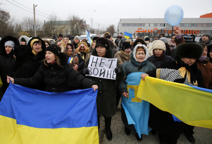 """Crimean Tatars shout slogans and hold banner which reads: """"No War"""" during the pro-Ukraine rally in Simferopol, Crimea, Ukraine, Monday, March 10, 2014. Russian President Vladimir Putin on Sunday defended the separatist drive in the disputed Crimean Peninsula as in keeping with international law, but Ukraine's prime minister vowed not to relinquish """"a single centimeter"""" of his country's territory. The local parliament in Crimea has scheduled a referendum for next Sunday. (AP Photo/Darko Vojinovic)"""