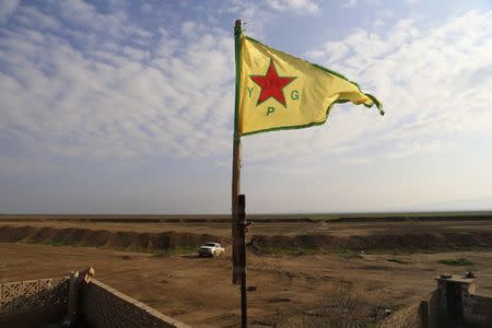 A Kurdish People's Protection Units (YPG) flag flutters on a lookout point between the Iraqi-Syrian border town of Rabia and the town of Snuny, north of Mount Sinjar December 20, 2014.REUTERS/Massoud Mohammed