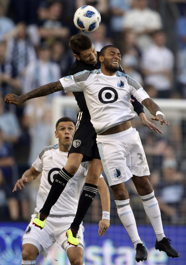 Minnesota United forward Alexi Gomez (32) heads the ball against Sporting Kansas City midfielder Ilie Sanchez, back, during the first half of an MLS soccer match in Kansas City, Kan., Sunday, June 3, 2018. (AP Photo/Orlin Wagner)