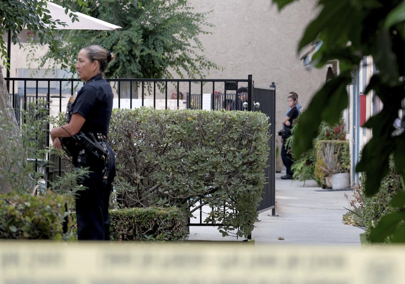 Los Angeles police officers guard an apartment where a shooting occurred in the Canoga Park area of Los Angeles on Thursday, July 25, 2019.  Police say a gunman shot five people, killing three, in two attacks in Los Angeles before he tried to rob someone outside a bank. (Dean Musgrove/The Orange County Register via AP)
