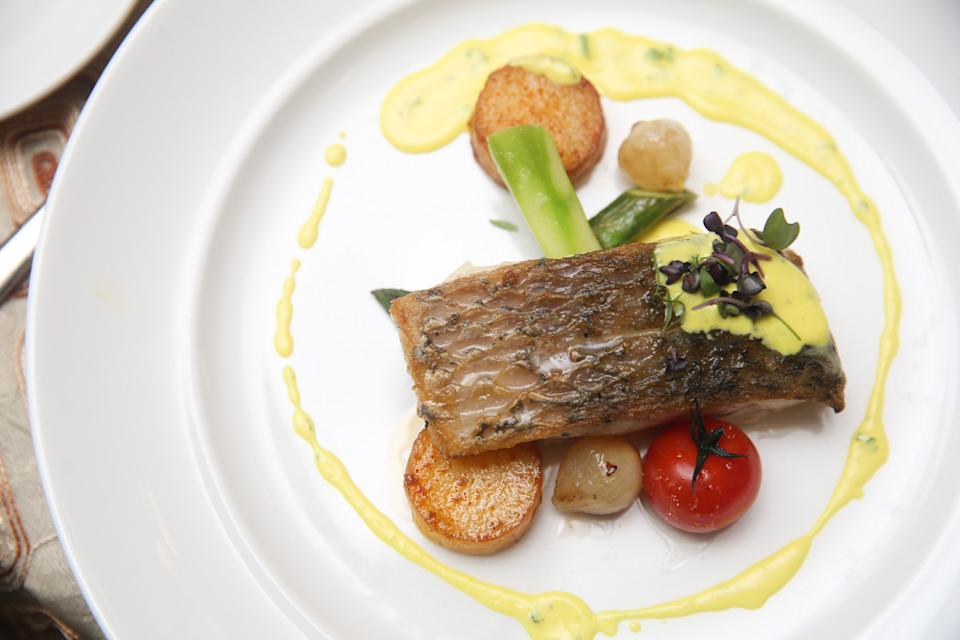 The baked sea bass filet is accompanied by ratatouille, baked black olive polenta, lemon butter sauce, balsamic, and herb salad. — Picture by Choo Choy May