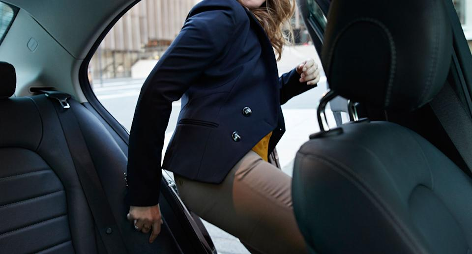 A woman enters the back of an Uber.