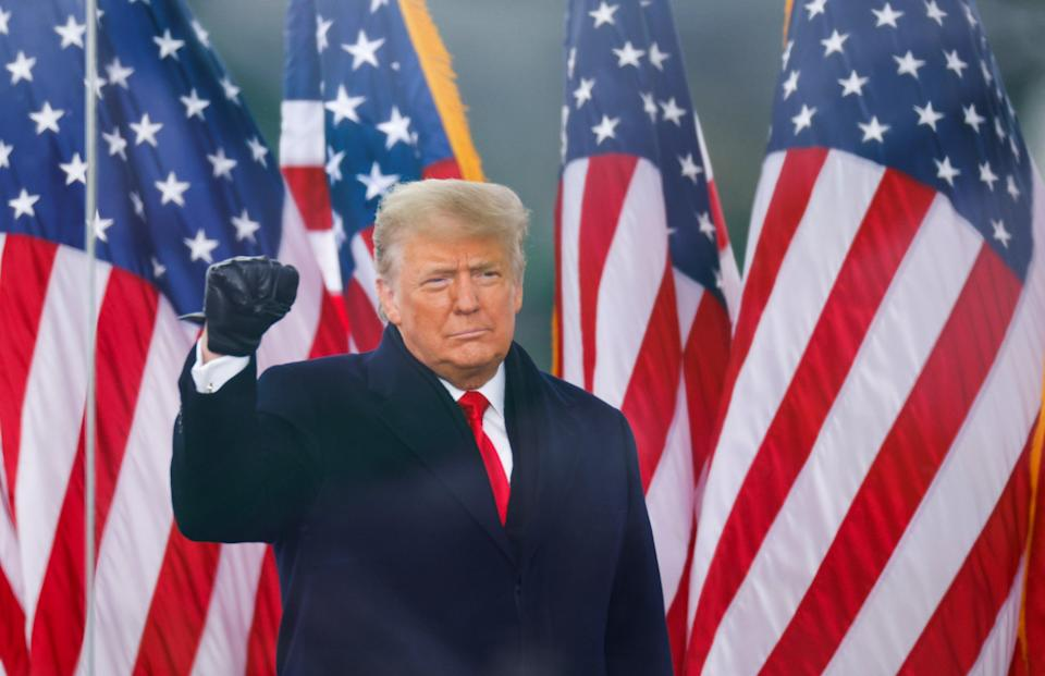 <p>Donald Trump makes a fist during a rally to contest the certification 2020 US presidential election</p> (Reuters)