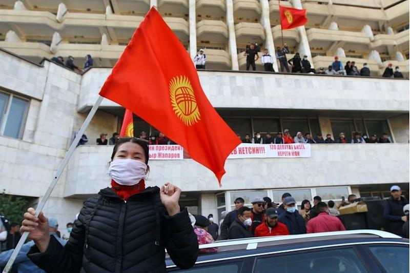 """A woman holds the national flag as supporters of Kyrgyzstan""""s Prime Minister Sadyr Japarov attend a rally in Bishkek, Kyrgyzstan October 15, 2020."""