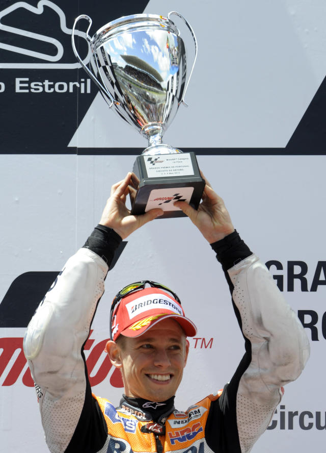 Repsol Honda team's Australian Casey Stoner celebrates on the podium after winning the Moto GP race of the Portuguese Grand Prix in Estoril, outskirts of Lisbon, on May 6, 2012. Stoner won the race ahead Spanish Jorge Lorenzo and Dani Pedrosa. AFP PHOTO / MIGUEL RIOPAMIGUEL RIOPA/AFP/GettyImages