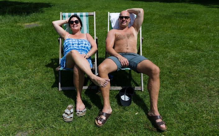 A couple sunbathing in deck chairs during the hot weather in Hyde Park - VICKIE FLORES/EPA-EFE/Shutterstock