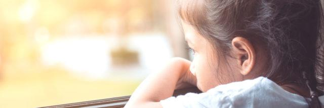 child looking sad by a window