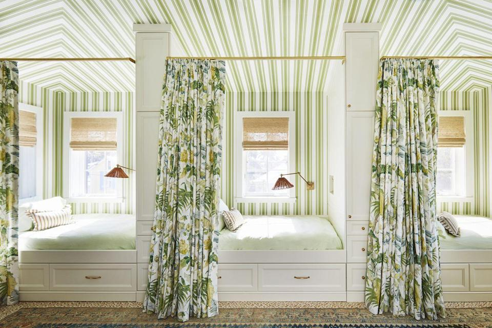 """<p>Tented striped wallpaper (<a href=""""https://go.redirectingat.com/?id=74968X1525088&xs=1&url=https%3A%2F%2Fwww.farrow-ball.com%2Fen-us&sref=https%3A%2F%2Fwww.veranda.com%2Fdecorating-ideas%2Fhouse-tours%2Fa35369885%2Fsummer-thornton-naples-house-tour-2021%2F&xcust=%5Butm_source%7C%5Butm_campaign%7C%5Butm_medium%7C%5Bgclid%7C%5Bmsclkid%7C%5Bfbclid%7C%5Brefdomain%7Cgoogle.com%5Bcontent_id%7C4f63b95f-8b64-4317-a79b-2978bf05cca9%5Bcontent_product_id%7C%5Bproduct_retailer_id%7C"""" rel=""""nofollow noopener"""" target=""""_blank"""" data-ylk=""""slk:Farrow & Ball"""" class=""""link rapid-noclick-resp"""">Farrow & Ball</a>) transforms a space over the garage at this Florida family retreat designed by Summer Thornton into a cabana-style guest quarters.</p>"""