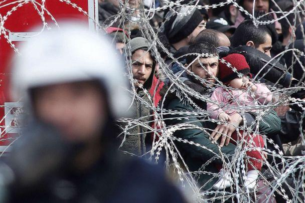 PHOTO: A man holding a child looks through barbed wire as migrants and refugees gather on the Turkish side of the closed Kastanies border crossing between Greece and Turkey, near the Evros River, in an attempt to cross into Greece, March 2, 2020. (Dimitris Tosidis/EPA via Shutterstock)