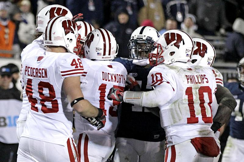 Wisconsin wide receiver Jeff Duckworth (15) celebrates with teammates as  Penn State linebacker Gerald Hodges, third from right, looks on after scoring a touchdown with 18 seconds to play in an NCAA college football game in State College, Pa., Saturday, Nov. 24, 2012. Penn State won 24-21 in overtime. (AP Photo/Gene J. Puskar)