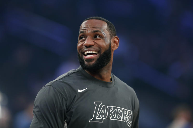 LeBron James smiles while looking off the photo with a blurred background.
