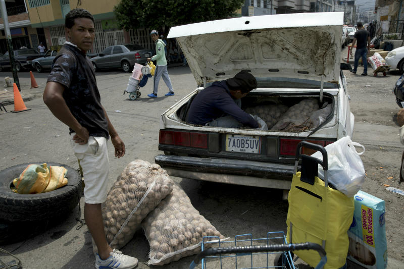 A man loads his car with potatoes bought in Colombia, in San Antonio del Tachira, Venezuela, on the border with Colombia, Thursday, Feb. 21, 2019. Opposition leaders led by self-proclaimed interim president Juan Guaido are vowing to bring in U.S. supplies of emergency food and medicine to dramatize the country's hardships under President Nicolas Maduro, who has said the country doesn't need such help. (AP Photo/Rodrigo Abd)