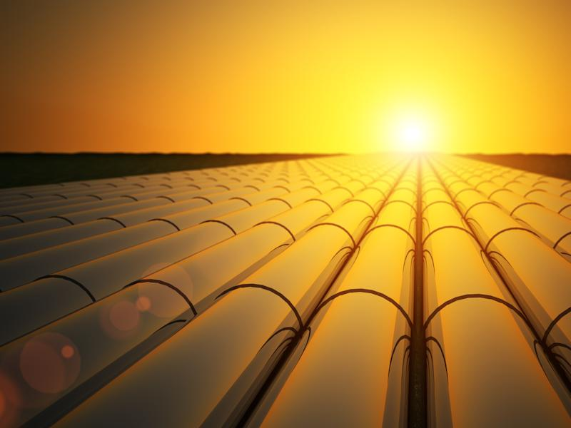 A row of oil pipelines with the sun setting in the distance.