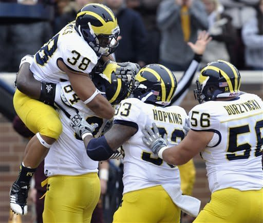 Michigan's A.J. Williams, second form left second, hoists running back Thomas Rawls (38) after Rawls scored a touchdown against Minnesota during the second quarter of an NCAA college football game, Saturday, Nov. 3, 2012, in Minneapolis. Michigan's Stephen Hopkins (33) and Joey Burzynski (56) join the celebration. (AP Photo/Tom Olmscheid)
