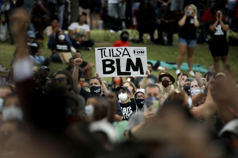 A woman holds up a sign as she listens to the Rev. Al Sharpton address the crowd at a Juneteenth rally in Tulsa, Okla., Friday, June 19, 2020. Juneteenth marks the day in 1865 when federal troops arrived in Galveston, Texas, to take control of the state and ensure all enslaved people be freed, more than two years after the Emancipation Proclamation. (AP Photo/Charlie Riedel)