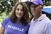 """Michele Hall stands with her husband, Doug, in their backyard Thursday, June 24, 2021, in Bradenton, Fla. Hall, 54, diagnosed with early Alzheimer's last year, calls the new drug Aduhelm """"the first tiny glimmer of hope"""" she'll get more quality time with her husband and their three adult children. (AP Photo/Steve Nesius)"""