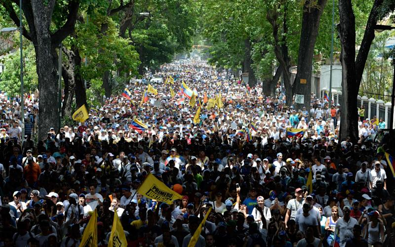 Thousands of demonstrators rally against Venezuelan President Nicolas Maduro in Caracas on April 19 - Credit: FEDERICO PARRA/AFP/Getty Images