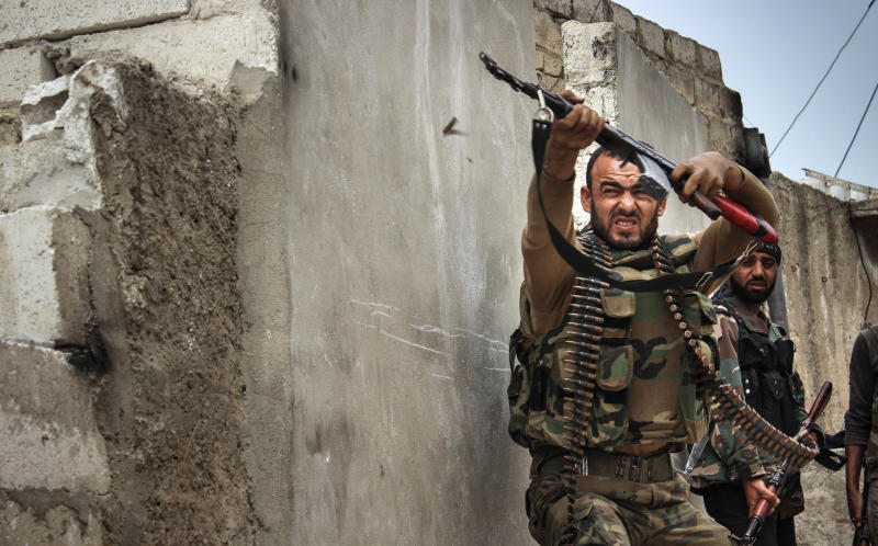 In this Tuesday, Oct. 30, 2012 photo, a Syrian rebel fires at sniper positions in the town of Harem, Syria, near the Turkish border. (AP Photo/Mustafa Karali)