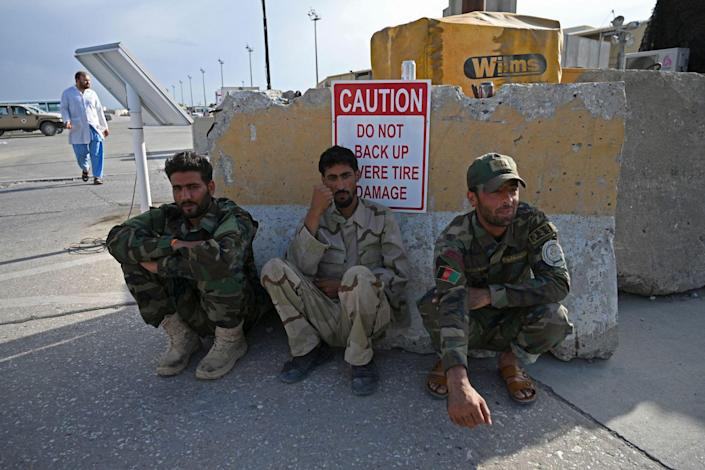 Three Afghan soldiers sit against a battered piece of concrete.