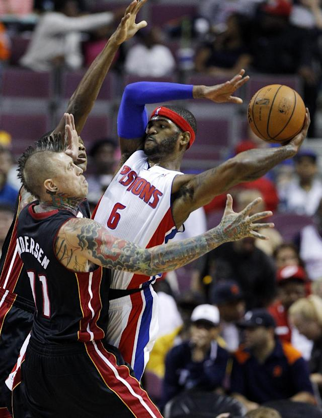 Detroit Pistons forward Josh Smith (6) tries to pass the ball against Miami Heat forward Chris Anderson (11) and James Jones, rear, in the first half of an NBA basketball preseason game on Thursday, Oct. 10, 2013, in Detroit. (AP Photo/Duane Burleson)