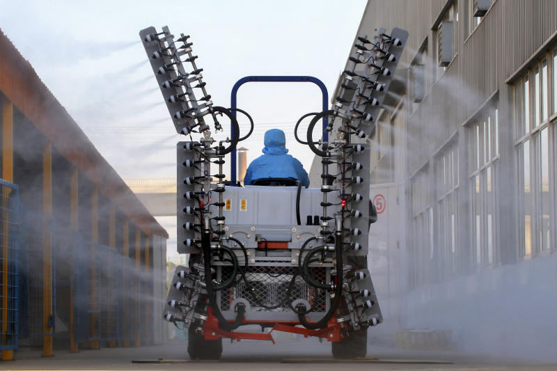 A worker in a tractor operates electrostatic spraying to disinfect the workplace following the coronavirus outbreak, in Yantai city in east China's Shandong province, Sunday, Feb. 9, 2020. China's virus death toll rose above 800, passing the number of fatalities in the 2002-2003 SARS epidemic, but fewer new cases were reported in a possible sign its spread may be slowing as other nations step up efforts to block the disease. (Chinatopix via AP)