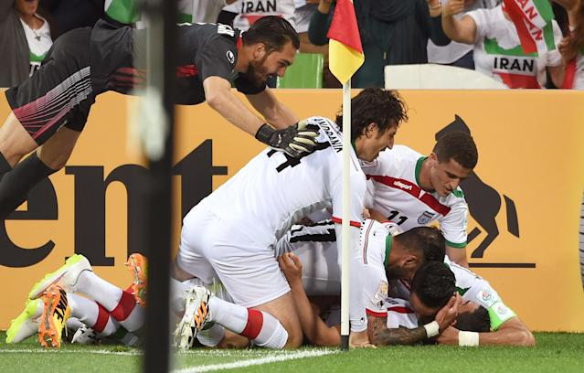 Iran's players celebrate after scoring against Bahrain during their AFC Asian Cup match, in Melbourne, on January 11, 2015 (AFP Photo/William West)