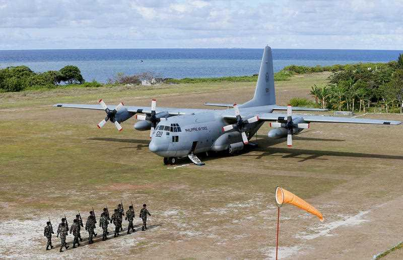 A file photo shows a Philippine Air Force C-130 transport plane as Philippine troops march at the Philippine-claimed Thitu Island off the disputed Spratlys chain of islands in the South China Sea in western Philippines.