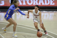 Washington State guard Krystal Leger-Walker (4) handles the ball while pressured by UCLA guard Chantel Horvat (0) during the first half of an NCAA college basketball game in Pullman, Wash., Friday, Feb. 5, 2021. (AP Photo/Young Kwak)