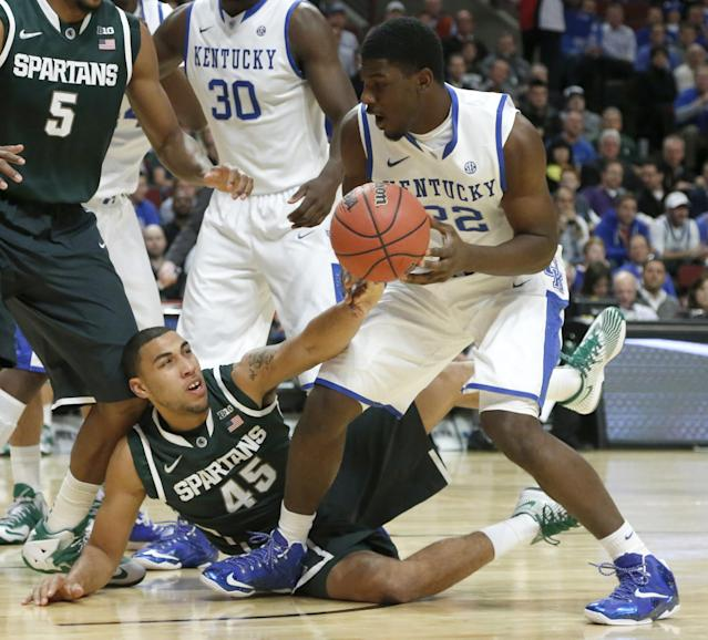 Michigan State guard Denzel Valentine (45) reaches for a rebound against Kentucky forward Alex Poythress during the first half of an NCAA college basketball game Tuesday, Nov. 12, 2013, in Chicago. (AP Photo/Charles Rex Arbogast)