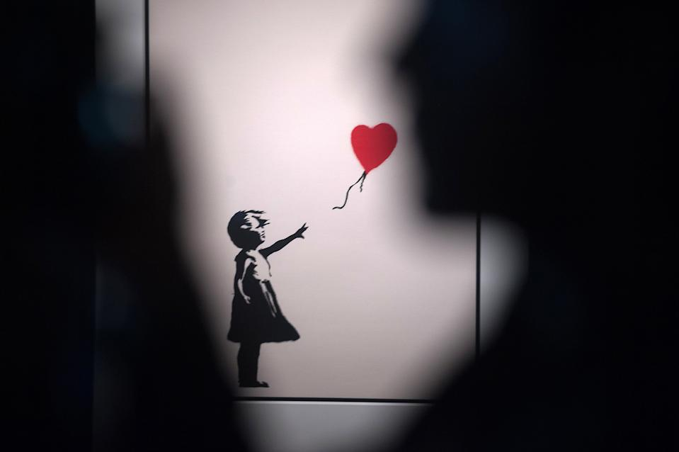 """A painting of 'Girl with a balloon' seen during the exhibition. 'Banksy The art of Protest' at cultural center 'La T�rmica' is an exhibition showing for the first time in Malaga. the work of famous and mysterious British street artist 'Banksy', display more than 40 creations such originals works, sculptures, videos and photographs provide by international private collections including the original print of """"Ni�a con globo"""". (Photo by Jesus Merida Luque / SOPA Images/Sipa USA)"""