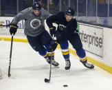 St. Louis Blues left wing Mackenzie MacEachern (28) and defenseman Vince Dunn (29) chase after a puck during NHL hockey practice at the Centene Community Ice Center in Maryland Heights, Mo., Monday, Jan. 4, 2021. (Colter Peterson/St. Louis Post-Dispatch via AP)