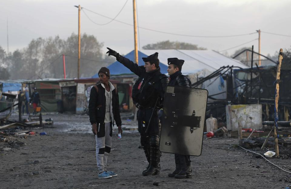 """FILE - In this Oct. 27, 2016, file photo, French police officers direct a migrant in the remains of the makeshift migrant camp known as """"the jungle"""" near Calais, northern France. Refugees who stayed at such camps during a 2015 wave of mass migration to Europe have lessons to share with the more than 124,000 people airlifted out of Afghanistan during the U.S.-led evacuation in 2021. (AP Photo/Emilio Morenatti, File)"""