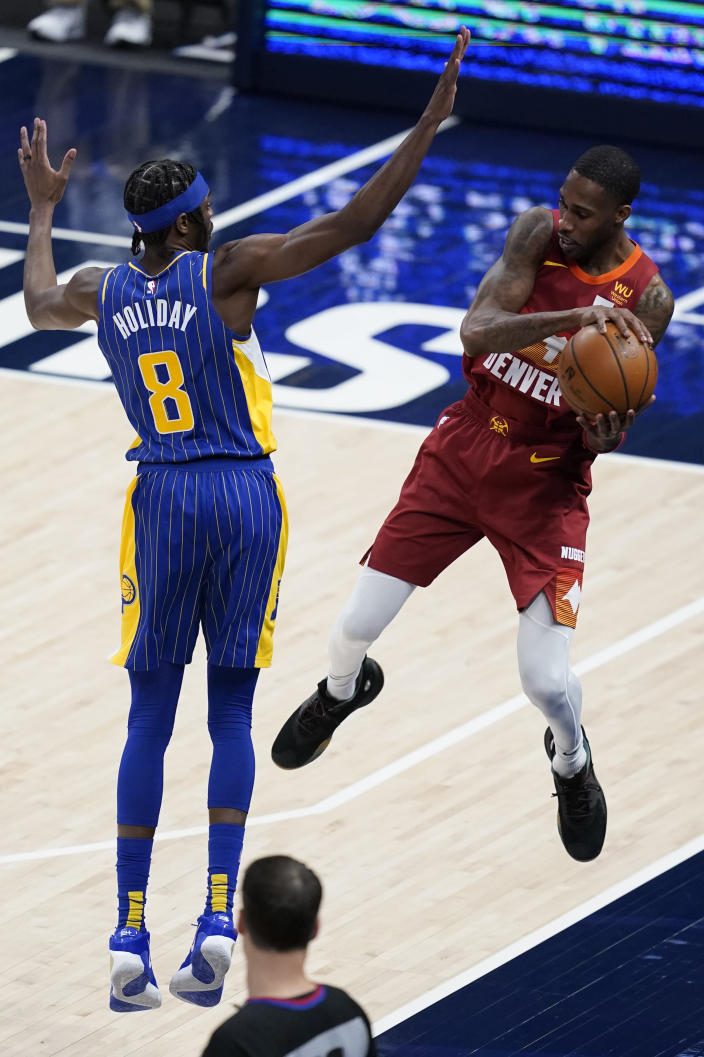 Denver Nuggets' Will Barton (5) throws the ball off Indiana Pacers' Justin Holiday (8) during the second half of an NBA basketball game Thursday, March 4, 2021, in Indianapolis. (AP Photo/Darron Cummings)